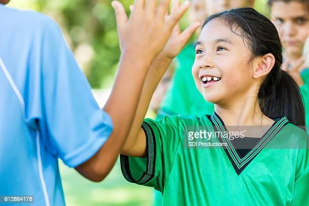 Elementary age Asian female soccer player greets opposing team