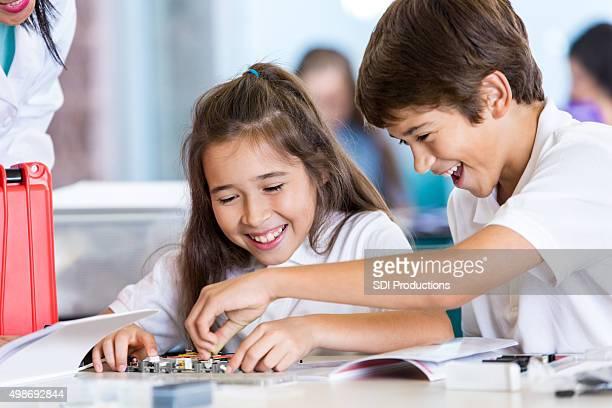 Di età scolare ragazzo e ragazza lavorando roobtics progetto
