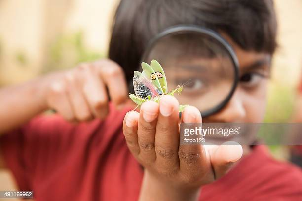 Elementary age boy enjoys discovering nature. Magnifying glass. Insect.