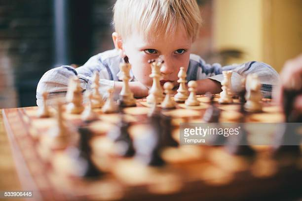Elementary age child playing, chess