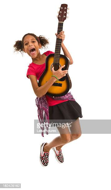 Elementary age female jumping in air and playing guitar