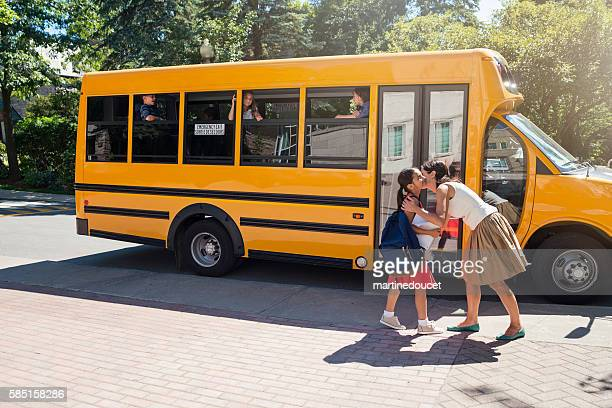 Elementary age girl kissing mother before getting on school bus.
