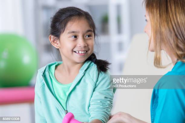 Elementary age girl works with physical therapist