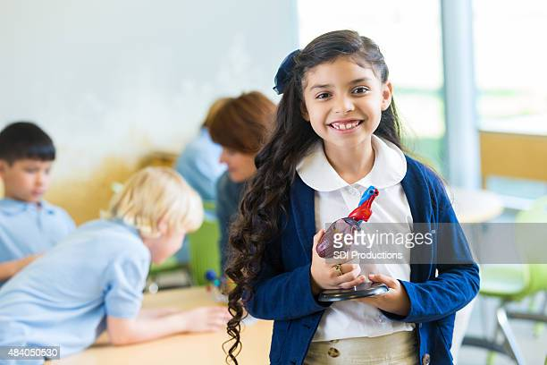 Elementary age Hispanic girl in private school science class