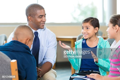Elementary age kids talking to counselor during group therapy session