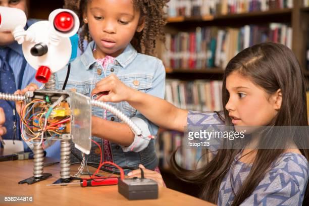 Elementary age school girls build robot in technology class.