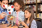 Elementary age African and Latin descent little girls work on building a robot in technology class in school classroom or library with male teacher assistance.  STEM topics.