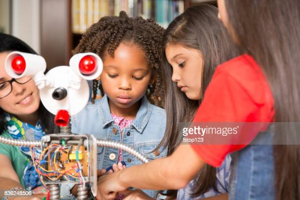 Elementary age school girls, teacher build robot in technology class.