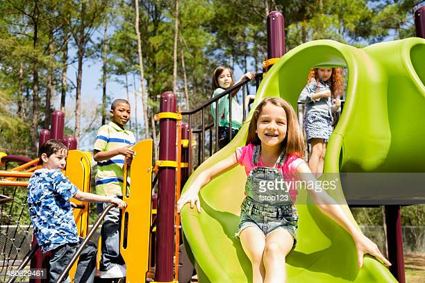Elementary children play at school recess or park on playground.
