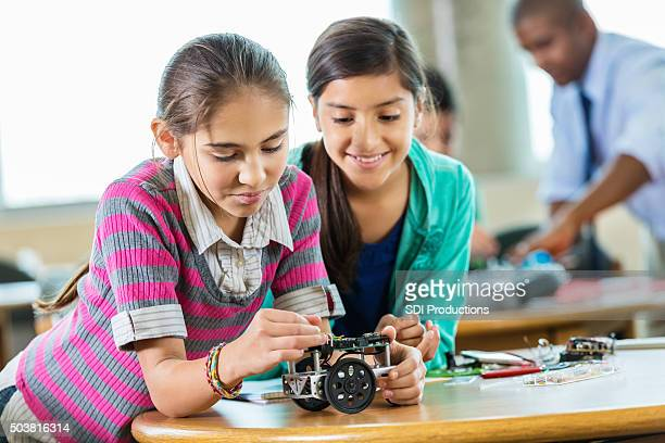 Elementary girls building robot in science and technology class