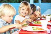 Elementary Pupils Enjoying Healthy Lunch In Cafeteria Sitting Down Smiling At Camera