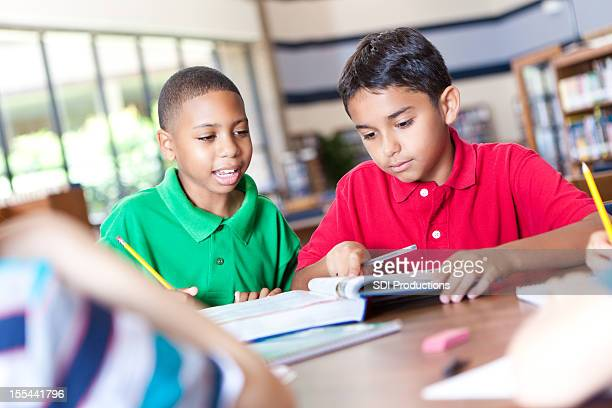 Elementary school age boys studying together for test