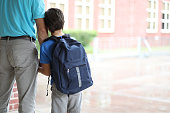 Father walks his young son to class on the first day of school.  Wearing a blue backpack, the unsure boy holds onto his dad.    Rear view.  Elementary school building in background.
