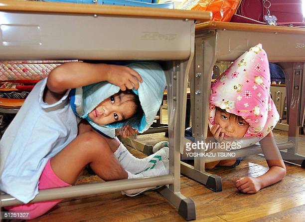Elementary school children crouch under their desks as part of a nationwide earthquake drill at a Tokyo elementary school 01 September 2004 The...