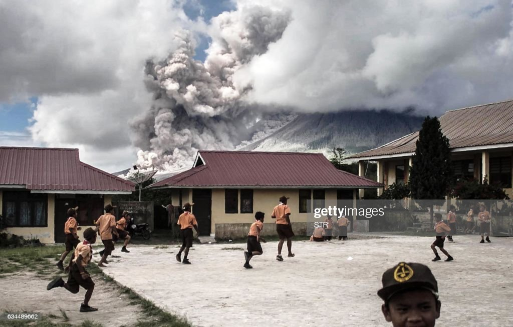 TOPSHOT - Elementary school children play outside of their classrooms as mount Sinabung volcano spews thick volcanic ash as seen from Karo, North Sumatra province, on February 10, 2017. Many residents in the area have been forced to relocate to other villages of Northern Sumatra at a safer distance from mount Sinabung volcano, one of the most active in Indonesia. /