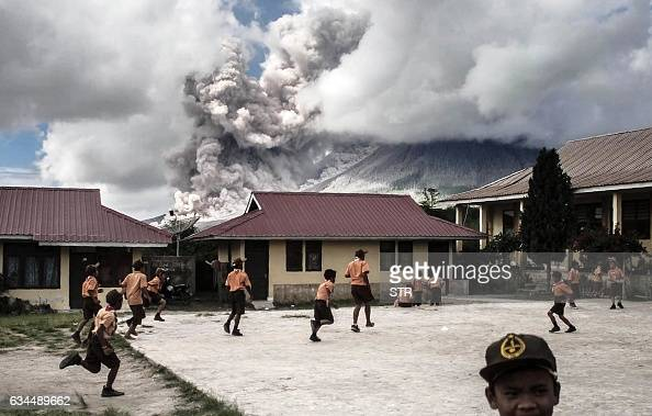 TOPSHOT Elementary school children play outside of their classrooms as mount Sinabung volcano spews thick volcanic ash as seen from Karo North...