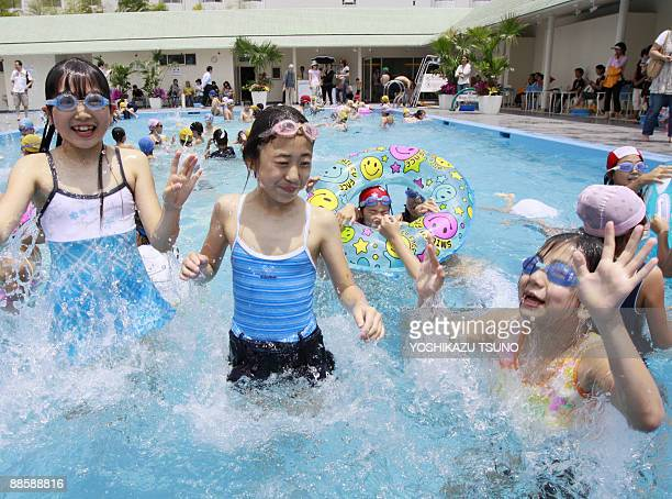 Elementary school children splash water in a swimming pool at Tokyo's ShinTakanawa Prince Hotel on June 20 2009 as the hotel opens its outdoor...