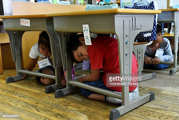 Elementary school children take cover under their desks during an earthquake drill at a school in Tokyo on September 1 2014 Nationwide antidisaster...