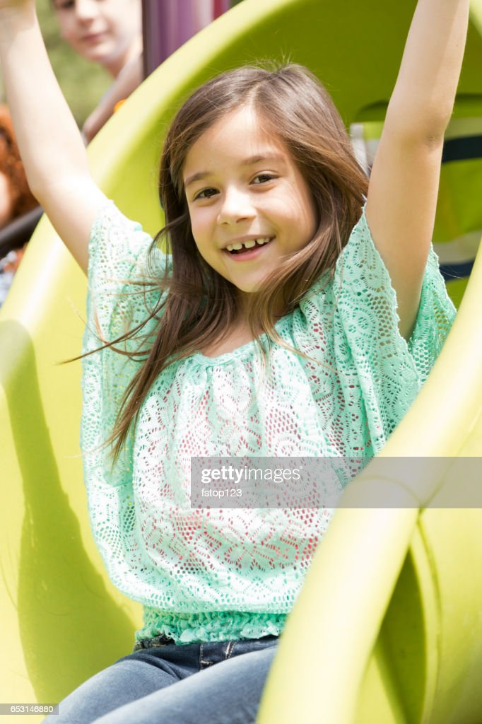 Elementary school girl playing on playground at park. : Stockfoto
