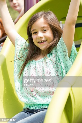 Elementary school girl playing on playground at park. : Stock Photo