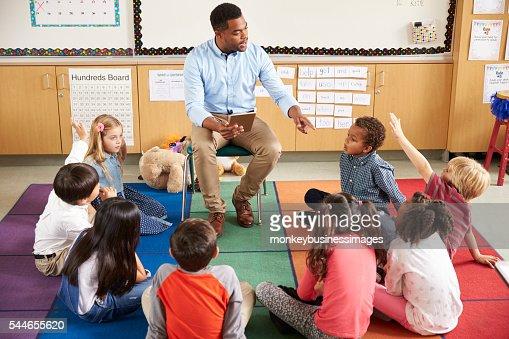Elementary school kids sitting around teacher in a lesson : Stock Photo
