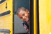 Elementary School Pupil Boarding Bus Looking Around Door