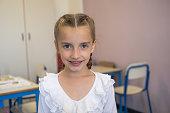 Pretty elementary school girl posing at camera