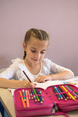 Pretty elementary school girl working on assignment in classroom