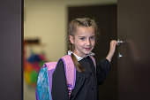 Elementary school student in uniform enters the classroom