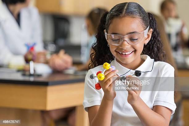 Studente di scuola elementare con l'Atomo modello scienze sperimentali