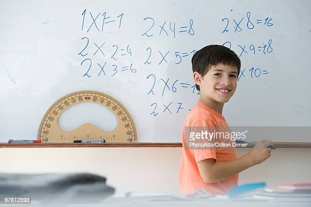 Elementary school student writing equations on whiteboard, smiling over shoulder at camera