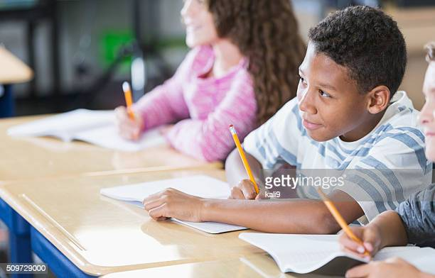 Elementary school students in class taking notes
