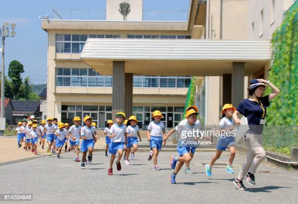 Elementary school students participate in an evacuation drill in the central Japan city of Takaoka on July 14 in the wake of repeated missile...