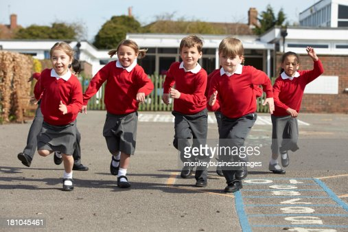 Elementary school students running in playground : Stock Photo