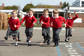 Elementary School Pupils Running In Playground Towards Camera