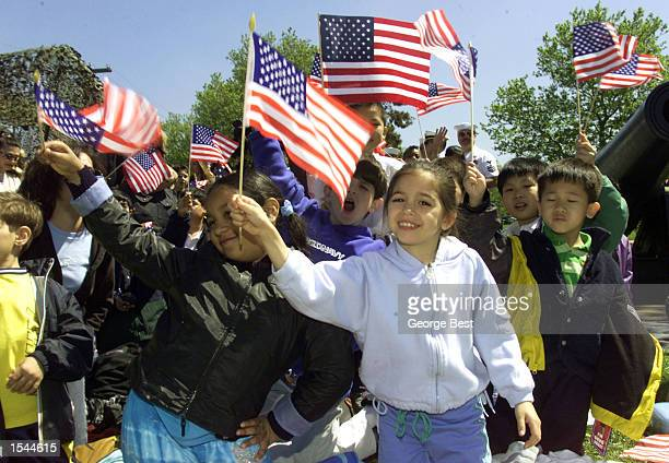 Elementary school students wave flags to welcome passing ships arriving for Fleet Week May 22 2002 in Brooklyn NY