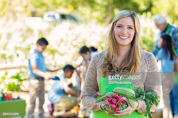 Elementary school teacher holding vegetables during science class