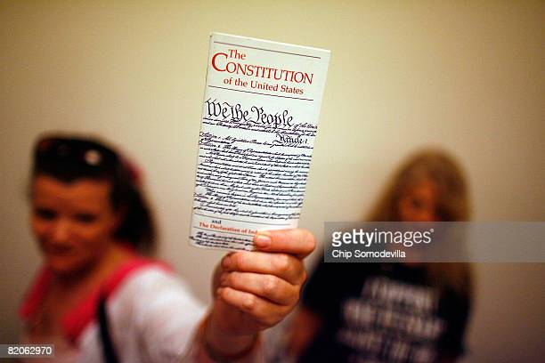 Elementary school teacher Lisa Petry of Virginia Beach Virginia holds up a copy of the US Constitution while waiting in line to attend the House...