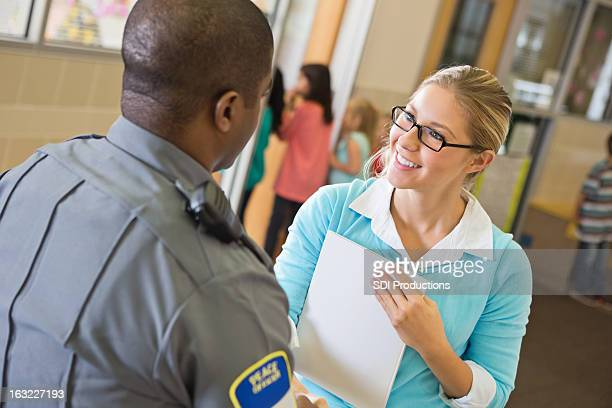 Elementary school teacher talking with police officer in hallway