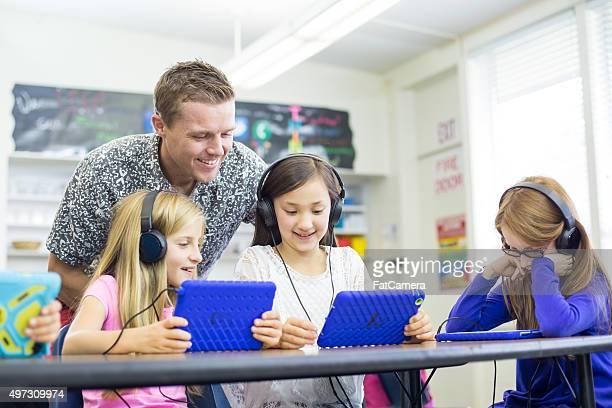 Elementary school teacher works with students on digital