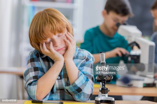Elementary schoolboy naps in science class