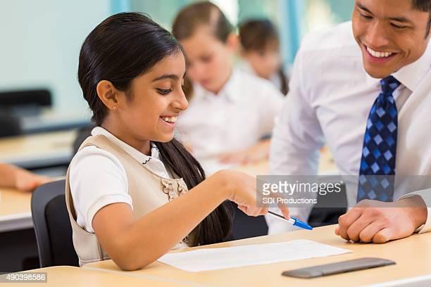 Elementary schoolgirl working on assignment with teacher
