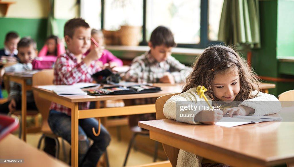 Écolière élémentaire écrit sur un cours dans la salle de classe. : Photo