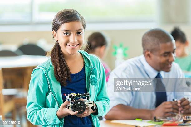 Elementary science student holding small robot she built