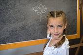 Elementary school student girl posing at the blackboard