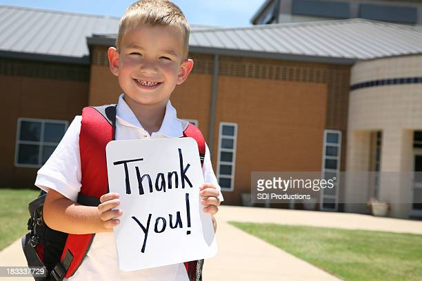 Elementary Student Holding Thank You Sign in Front of School
