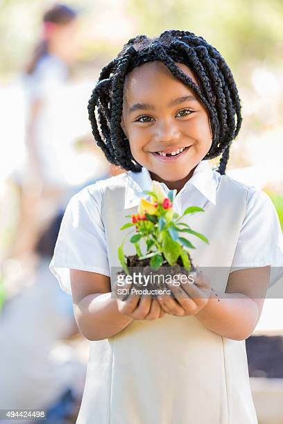 Elementary student learning about plant life in school garden