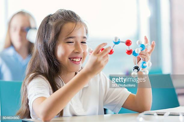 Elementary student studying molecule model in modern science class