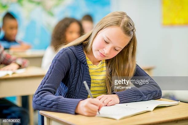 Elementary Student Writing in Notebook