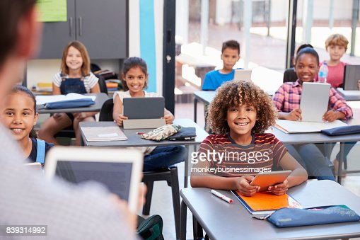 Elementary students looking at teacher, over shoulder view : Stock Photo